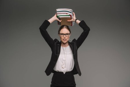 angry female teacher in eyeglasses holding stack of textbooks over head isolated on grey background
