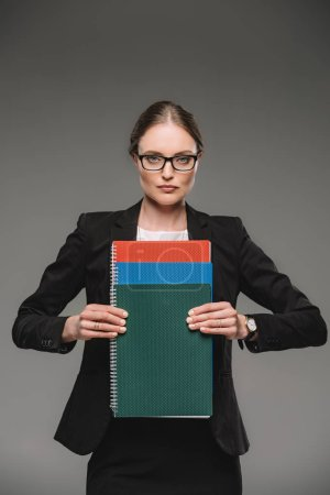 serious female teacher in eyeglasses holding textbooks isolated on grey background