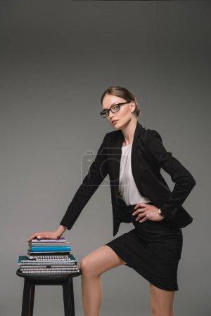 female teacher in eyeglasses standing near stack of textbooks on chair on grey background