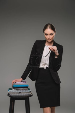 confident female teacher standing near chair with stack of textbooks on grey background