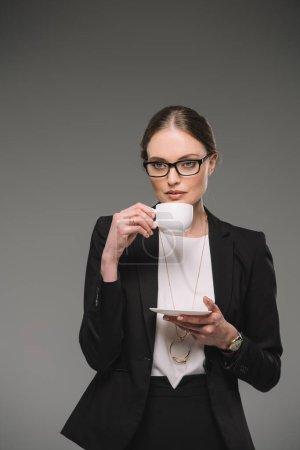 attractive businesswoman in eyeglasses drinking coffee from cup isolated on grey background