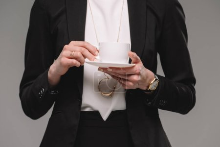 cropped image of businesswoman holding cup of coffee isolated on grey background