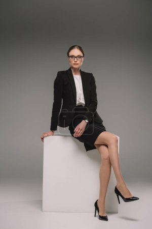 serious businesswoman in eyeglasses sitting on cube on grey background