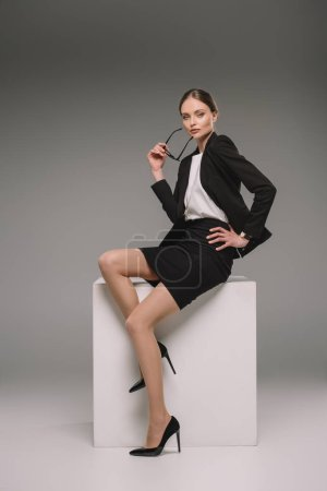confident businesswoman holding eyeglasses and sitting on cube on grey background