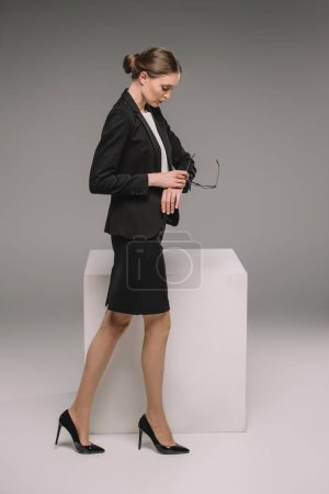 businesswoman holding eyeglasses and looking at wristwatch near cube on grey background