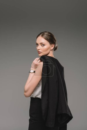 businesswoman holding jacket over shoulder isolated on grey background