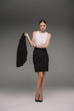 attractive businesswoman holding jacket on grey background