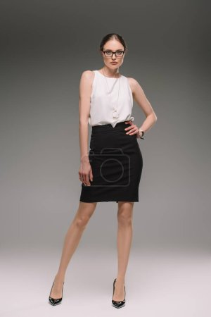 Photo for Attractive businesswoman in eyeglasses posing on grey background - Royalty Free Image
