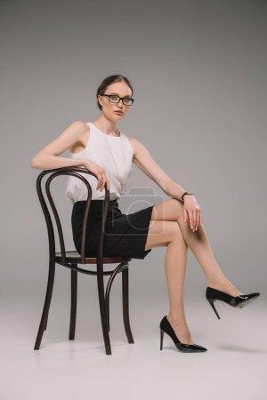 attraktive Geschäftsfrau mit Brille sitzt auf einem Stuhl und blickt in die Kamera auf grauem Hintergrund