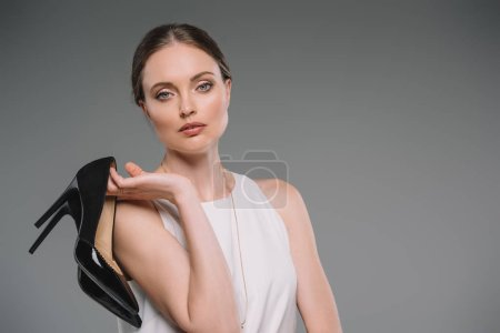 portrait of attractive businesswoman looking at camera and holding shoes with high heels isolated on grey background