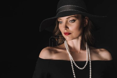 beautiful woman in black straw looking away isolated on black background