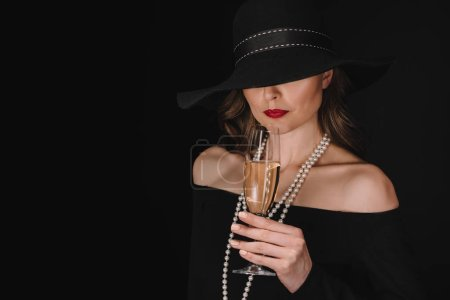beautiful elegant woman with eyes covered by black straw holding champagne glass isolated on black background