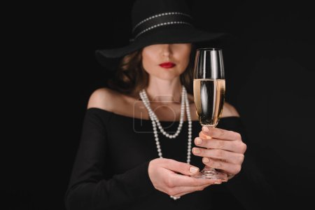Photo for Selective focus of champagne glass in hands of elegant woman with covered eyes by straw isolated on black background - Royalty Free Image