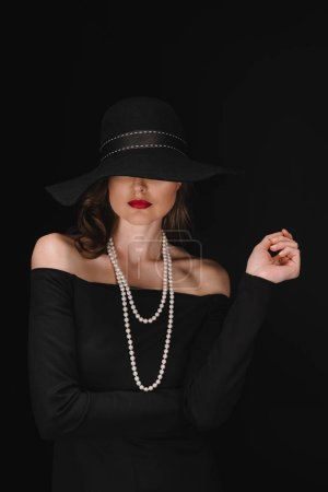 beautiful woman with eyes covered by black straw isolated on black background