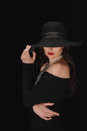 Photo for Elegant woman in black dress with eyes covered by straw isolated on black background - Royalty Free Image