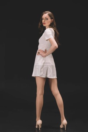 beautiful female model in dress posing isolated on black background
