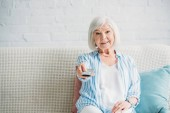 portrait of smiling senior woman with remote control watching tv on sofa at home