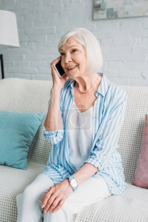 portrait of smiling senior woman sitting on couch and talking on smartphone at home