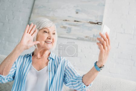 side view of cheerful senior woman taking selfie on smartphone at home