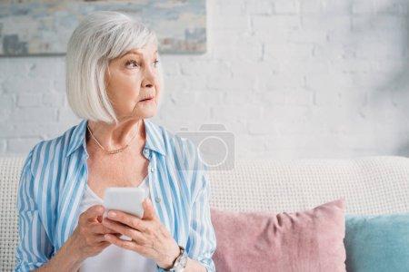 Photo pour Portrait de femme âgée coûteuse avec smartphone regardant ailleurs reposant sur le canapé à la maison - image libre de droit