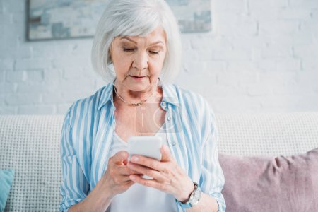 portrait of senior woman using smartphone while resting on couch at home