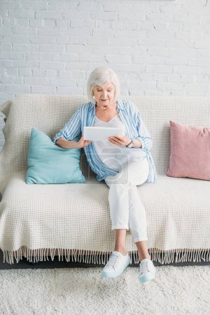 senior woman using tablet while resting on couch at home