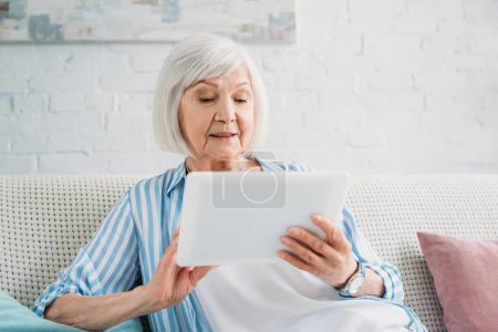 Photo for Portrait of senior woman using tablet on sofa at home - Royalty Free Image