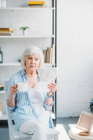 portrait of senior woman with cup of coffee using tablet at home