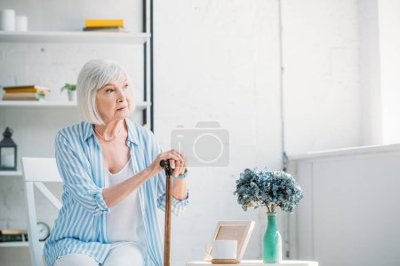 portrait of thoughtful senior woman with walking stick looking away at home