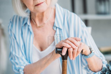 partial view of senior lady with wooden walking stick at home