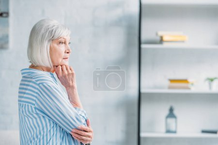 side view of beautiful pensive senior lady in stylish clothing looking away at home