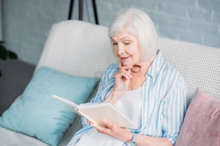 senior woman reading book while resting on sofa at home