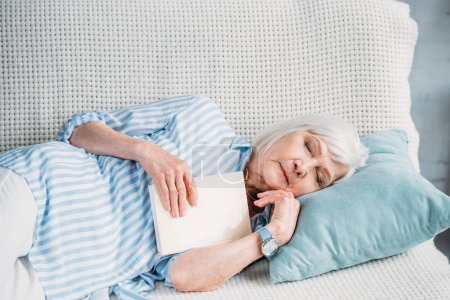 Photo pour Portrait d'une femme senior avec livre dormir sur le canapé à la maison - image libre de droit