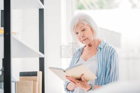 portrait of grey hair woman reading book near bookshelf at home