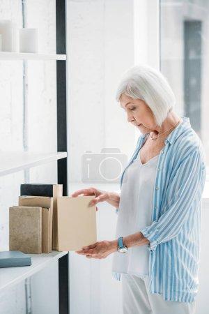 side view of senior woman arranging books on bookshelf at home