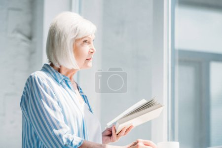 side view of grey hair woman with book and cup of coffee standing at windowsill at home