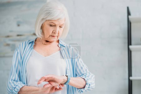 portrait of senior lady in stylish clothing checking time at home
