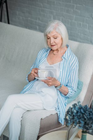 senior woman with cup of aromatic coffee resting on sofa at home