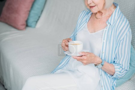 partial view of senior woman with cup of aromatic coffee sitting on sofa at home