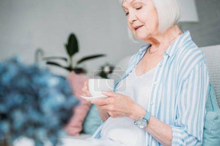 vue latérale d'une femme senior avec une tasse de café aromatique à la maison
