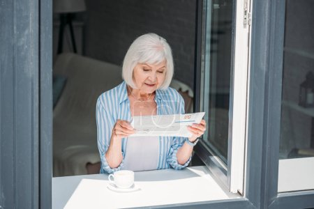 senior woman standing at windowsill with cup of aromatic coffee and reading newspaper at home