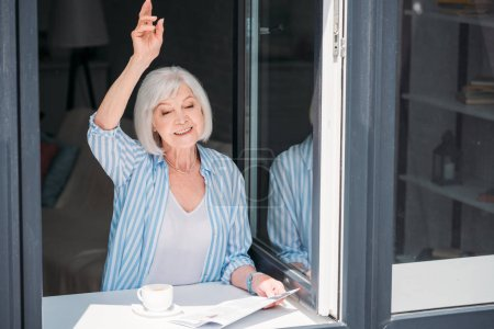 senior woman greeting someone while standing at windowsill with newspaper and cup of aromatic coffee at home
