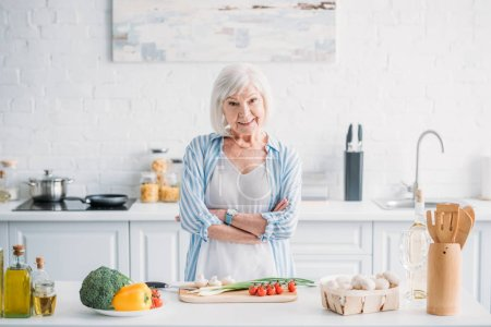 portrait of smiling senior with arms crossed standing at counter with fresh vegetables in kitchen