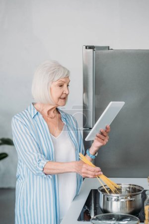 side view of senior woman with digital tablet cooking macaroni in kitchen at home