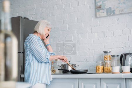 side view of smiling senior woman talking on smartphone while cooking dinner in kitchen