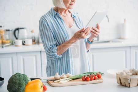 partial view of senior woman with digital tablet standing at counter with fresh vegetables in kitchen