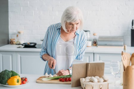 portrait of senior lady looking for recipe in cookery book while cooking dinner at counter in kitchen