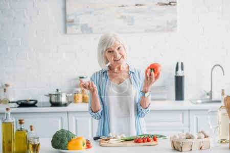 portrait of smiling grey hair lady with bell pepper in hand standing at counter in kitchen