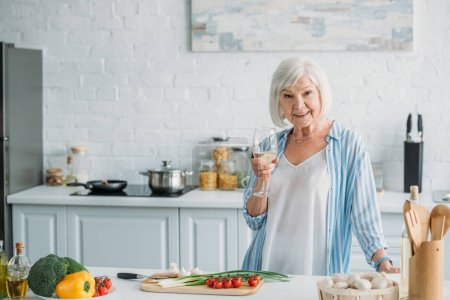 portrait of smiling senior lady with glass of wine standing at counter with fresh vegetables in kitchen