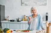 Portrait d'une dame senior souriante avec verre de vin debout au comptoir avec des légumes frais dans la cuisine